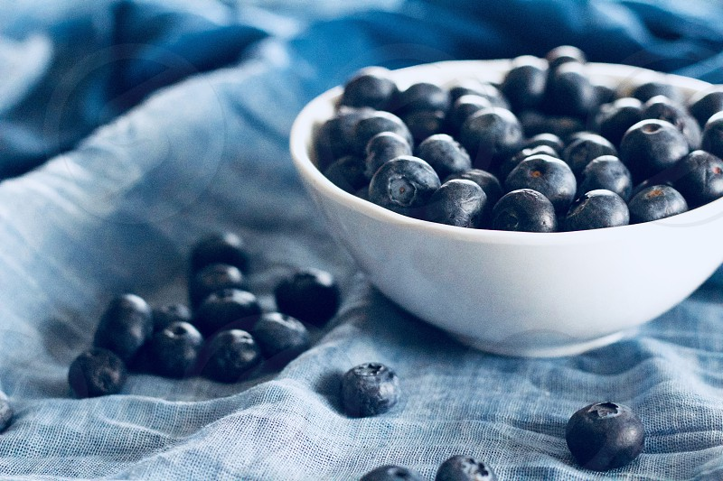 On the Table - Blueberries in a white bowl and scattered on gradated blue fabric photo