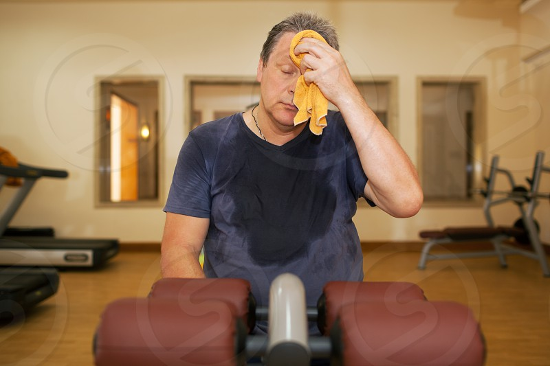 Exhausted mature man wiping sweat with a towel after intensive training in the gym photo