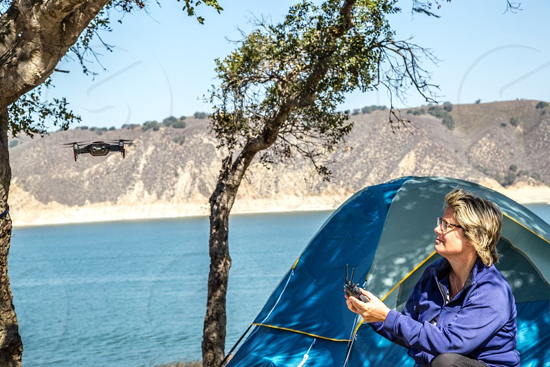 Woman flying a drone at camp site photo