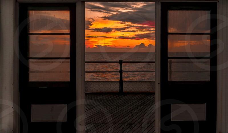Door sunset sky clouds sun colour frame view framed pier ocean photo