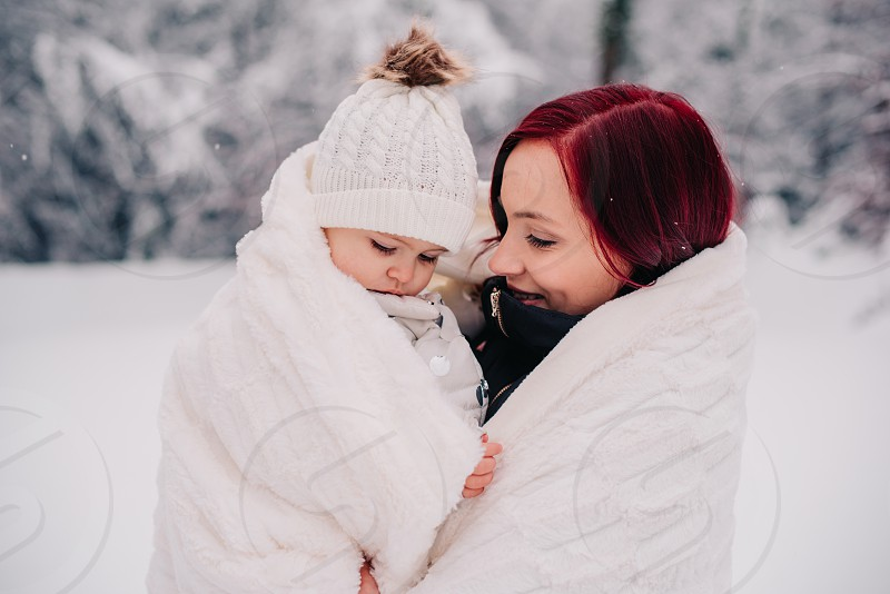Mother and her baby wrapped in warm white blanket to warm themselve up. photo