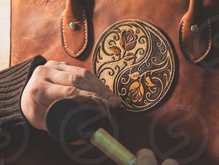 Close up hands of unrecognizable leather craftsman working on measurements in patterns in local workshop studio. Small business. Brown fancy tooled floral texture for background. photo