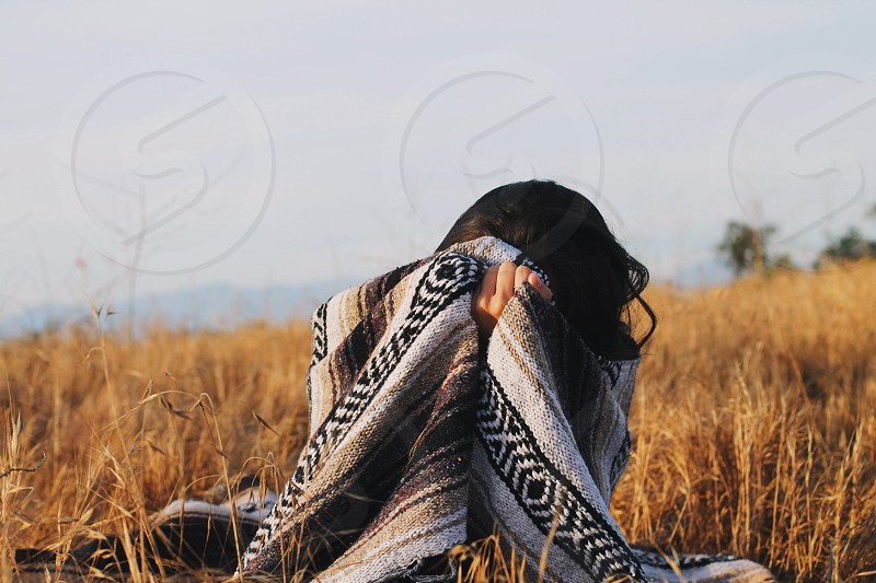 woman sitting on brown grass field using a grey brown and black tribal cloth under grey skies photo