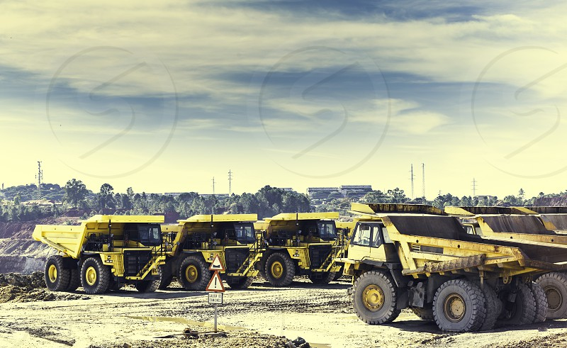 Yellow dumper trucks in mine of Riotinto put in row with traffic signal of exit of trucks in foreground and blue sky background and clouds photo