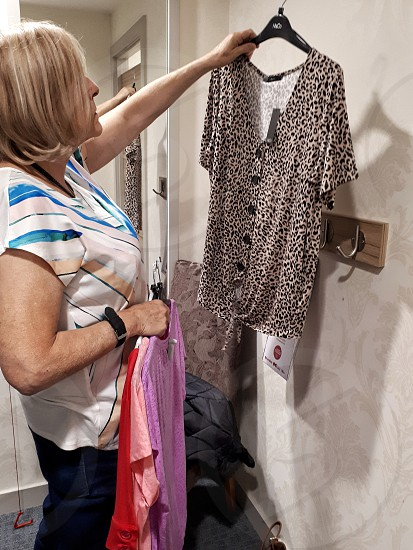 Middle aged woman in a store changing room examing clothes... photo