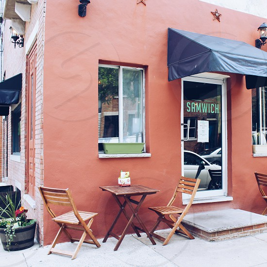 2 brown wooden folding chairs and folding table outside samwich shop photo