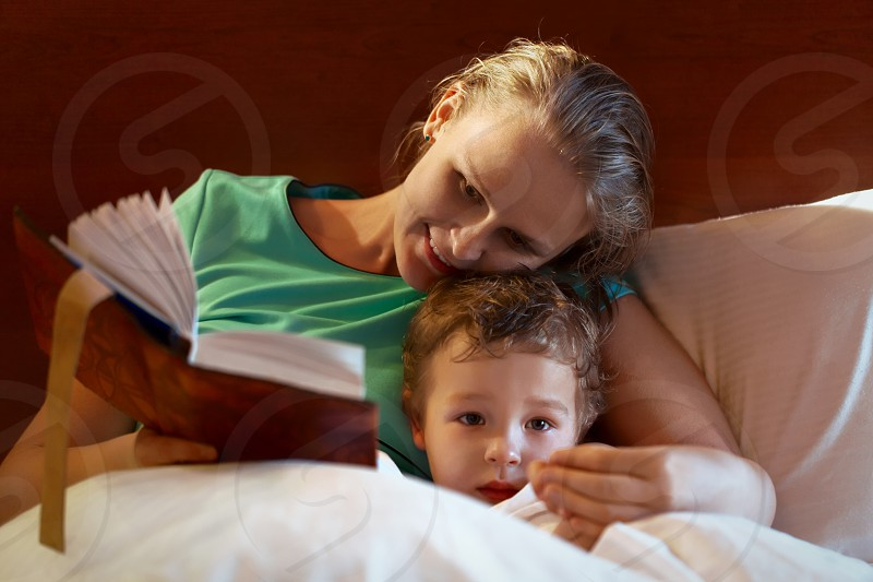 Young mother reading from a thick book to her child in bed smiling as she tells the story as the child peers over the bedclothes at the camera with a serious expression photo