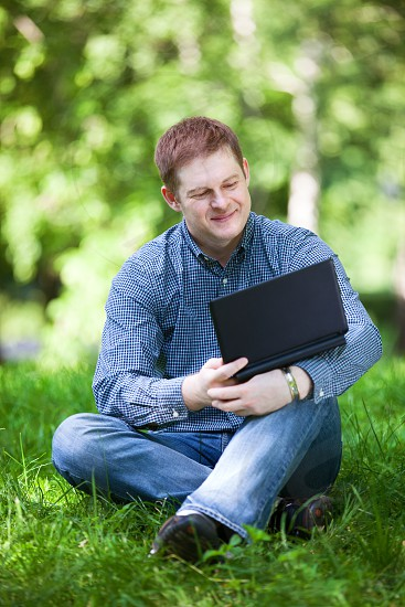 Successful smiling businessman working with laptop in the city park. photo