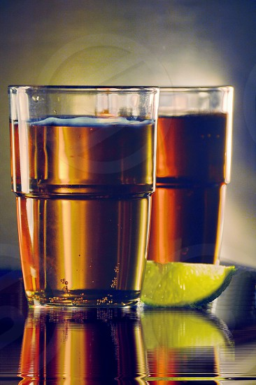 Two glasses of beer one pale the other a darker blend of beer. A lime wedge. On a tray of water reflecting the glasses. photo