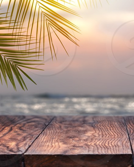 Landscape vintage nature background of coconut palm tree on tropical beach sunset sky with vintage old wood table top shelf perspective view for promote product concept. photo