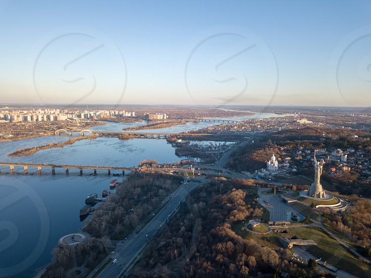 Aerial view from the drone to the Dnieper River with modern architecture the Motherland Monument Patona Bridge Darnytskyy Mist South Bridge in Kiev Ukraine. photo