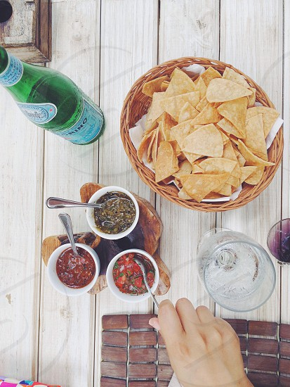 Fresh homemade tortilla chips and salsa fresca trio at lunch on the beach in Tulum Quintana Roo Mexico. Pellegrino water sandy feet and a tropical vacation.  photo