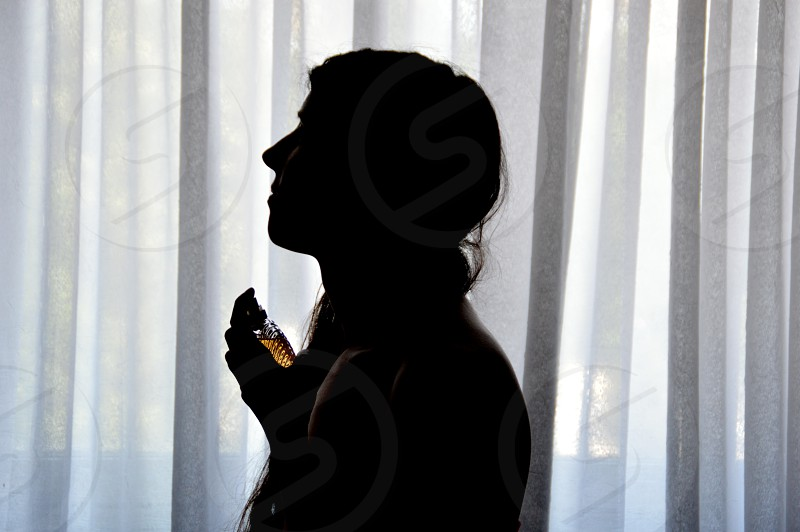 Silhouette of the young woman against the window light photo
