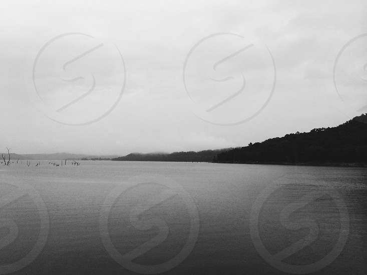 grayscale photo of lake over mountain view photo