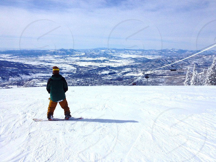 Snowboarder on top of the mountain looking at the view. photo