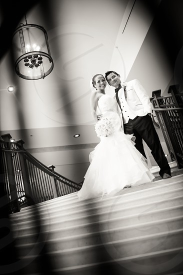couple wearing wedding attire standing on staircase smiling photo