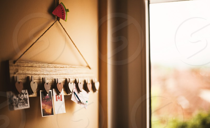 Behind the window in a kid's room interesting hanger with clothespins with wooden hearts.  photo
