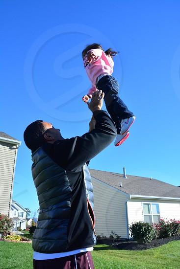 man throwing child up photo