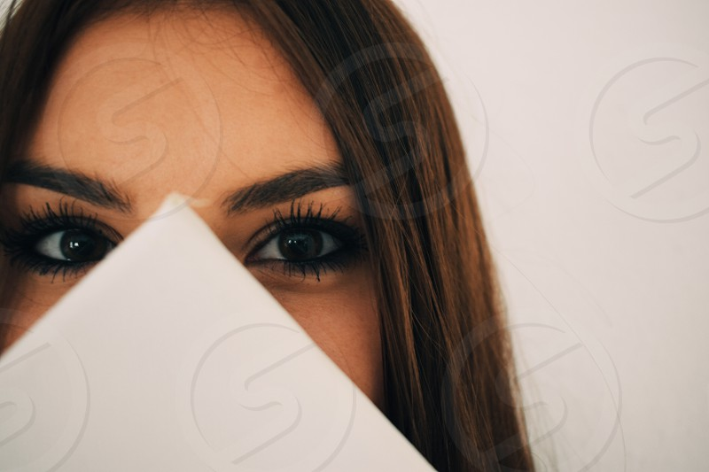 face of a woman hidden behind eyes looking at you photo