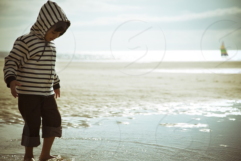 kid outdoor at the beach playing with the sea wet feet wearing marine sweater with boat background on sunny summmer day photo