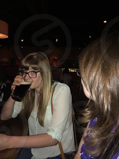Blonde young woman drinking a beer at a bar photo