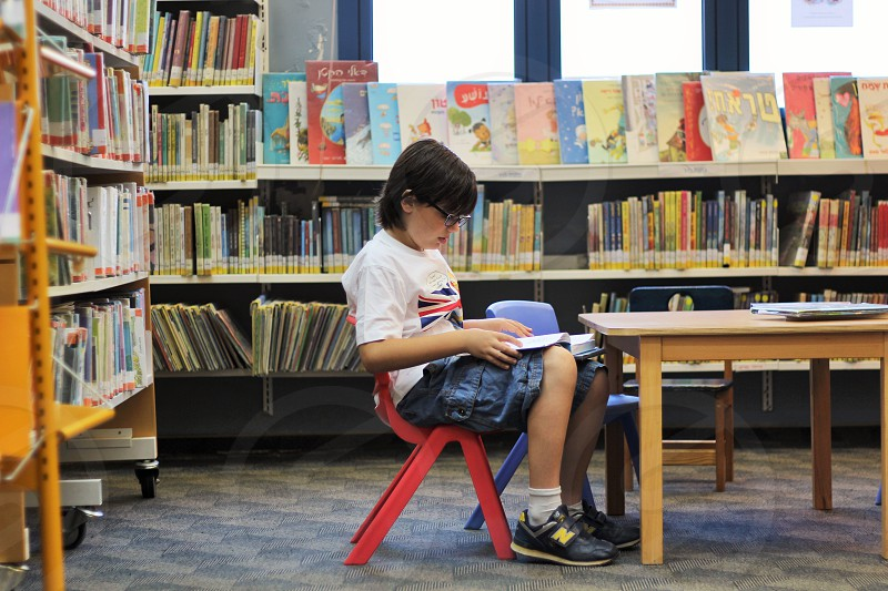 kid sitting and reading a book photo