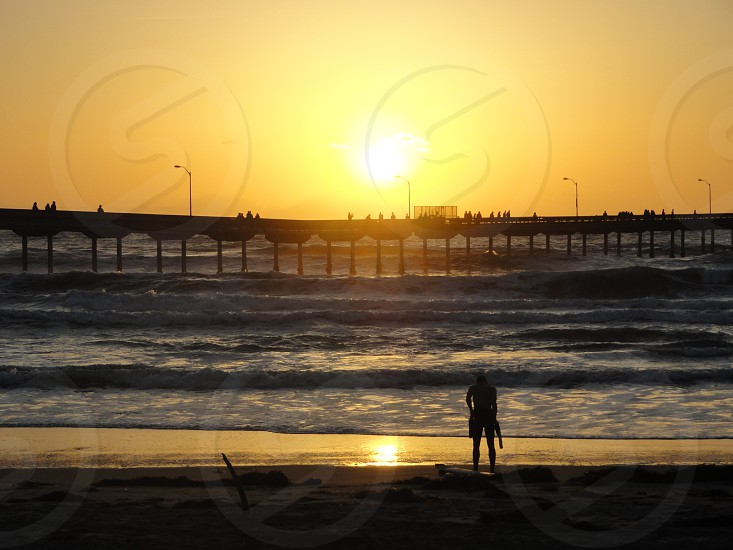 man silhouette standing on seashore photo