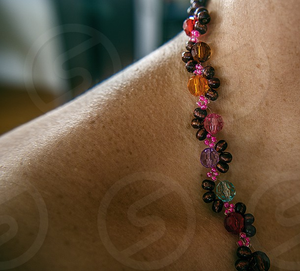 A closeup shot of a beaded necklace on a woman's neck. photo