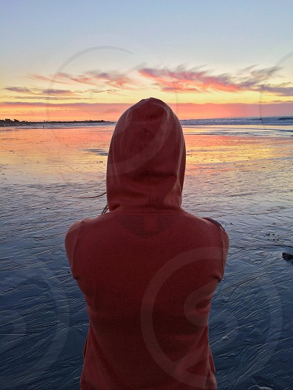 man in orange hoodie with sunset view photo