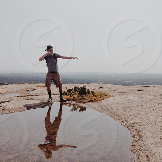 man dancing near water reserve on rocky mountain photo