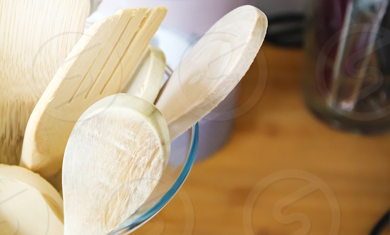 Close-up view of a group of wooden kitchen utensils inside a glass container. Cooking with traditional utensils photo