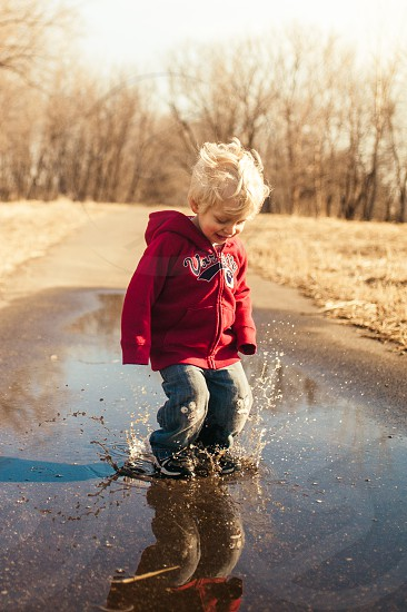 A boy enjoying his youth while jumping in puddles outside in the fall. photo