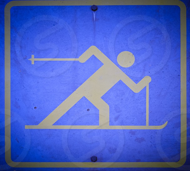 Blue pictorial skiing signboard depicting a very dynamic person on skis x-country skiing to mark a track against a leafy green background photo