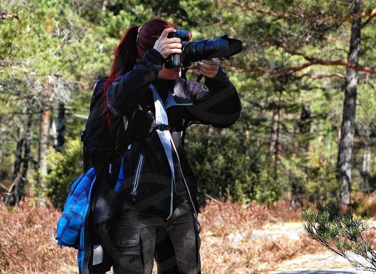 woman in black zip up jacket holding black dslr camera taking photos photo