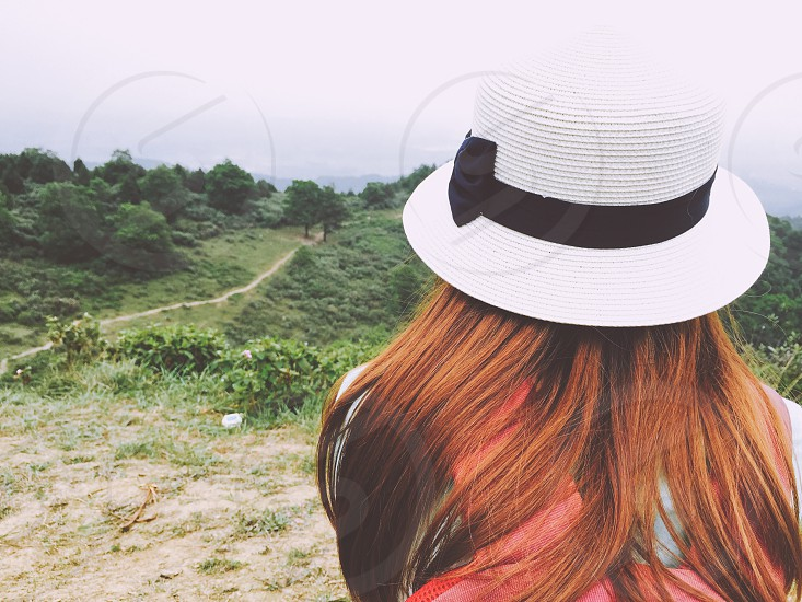 girl wearing black and white bowtie accent hat facing green field during daytime photo
