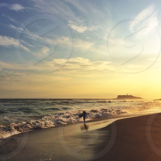 view of white skies and man walking on beach photo