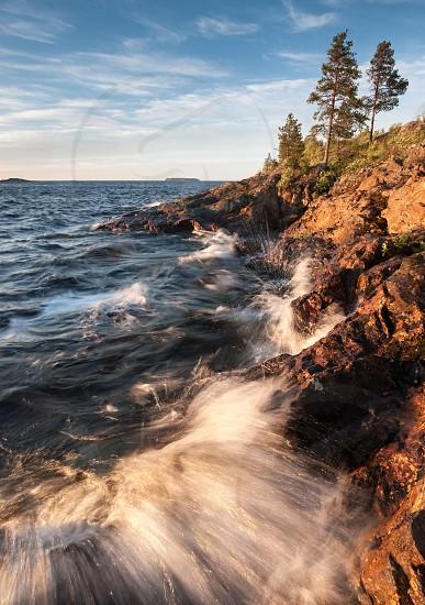 Surf on stony coast of lake with waves under sunrise light at morning natural landscape photo
