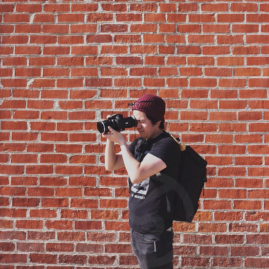 person in black shirt using a camera photo