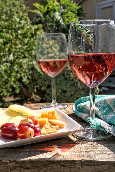 Rose wine  cheese and grapes in an outdoor setting photo