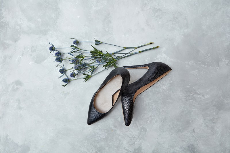 blue flowers and black female shoes on a gray background the concept of Valentine's Day top view photo