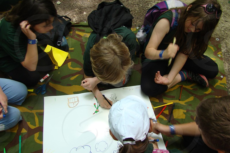 A group of kids drawing on a piece of paper.                                photo