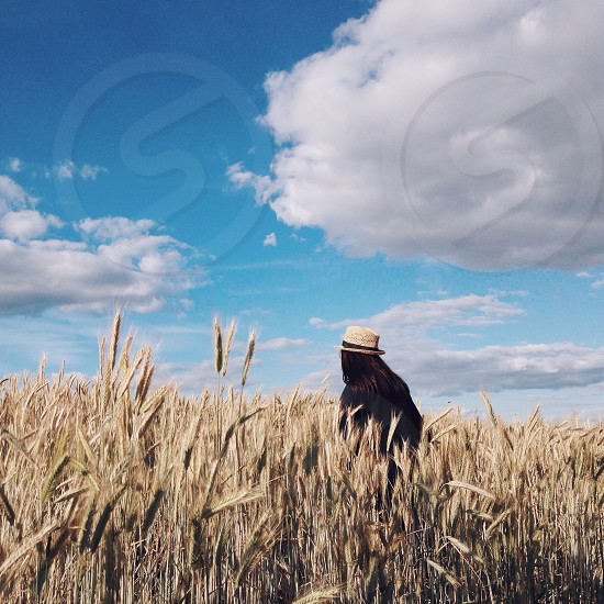 woman wearing white hat standing in field photo