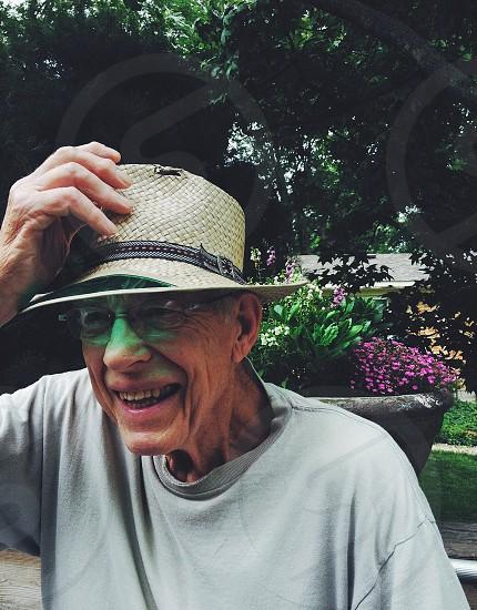 man wearing beige straw hat smiling photo