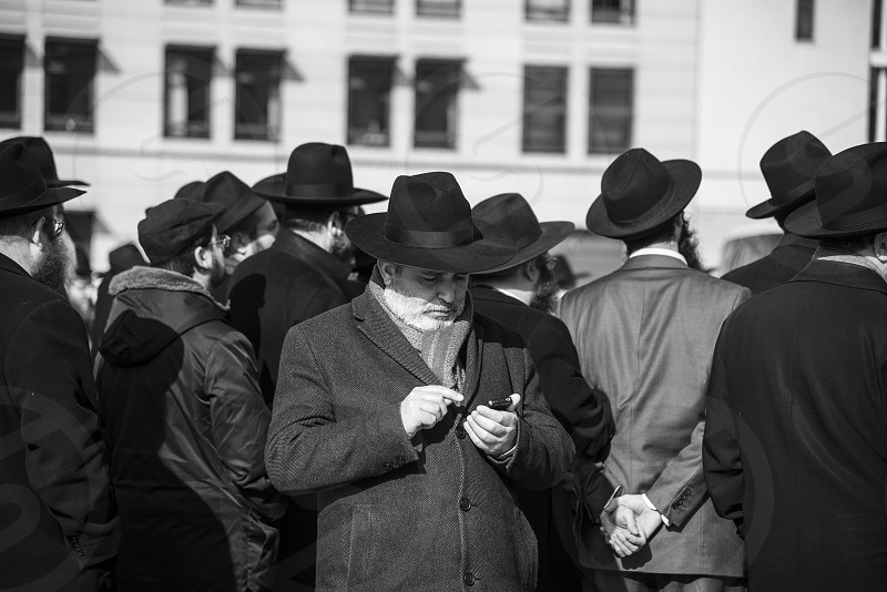 Man on phone being crowd of other men photo