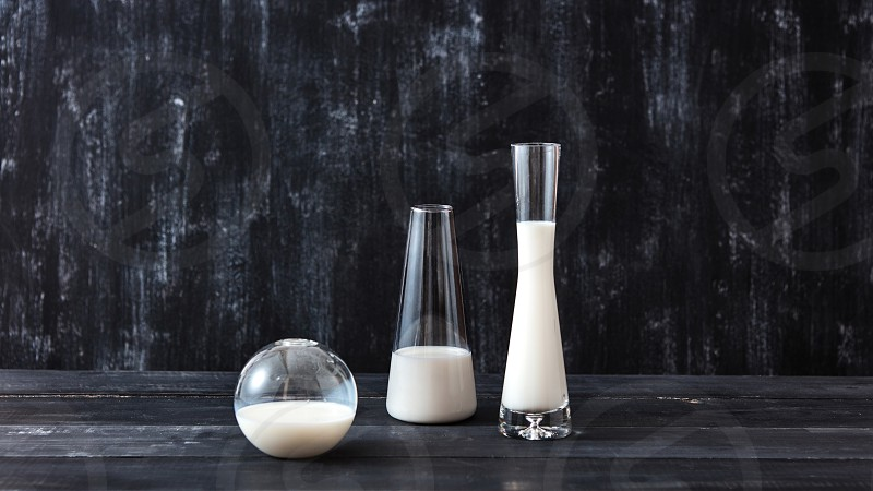 Containers of glass cone and spherical shape filled with white liquid on a dark wooden table on a black background with place for text. Jewish holiday Shavuot concept. photo