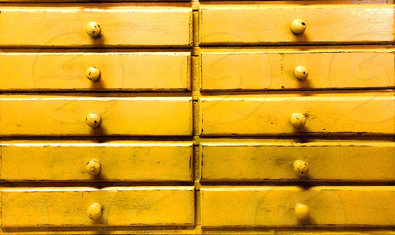 Detail of the drawers on a yellow vintage chest. photo