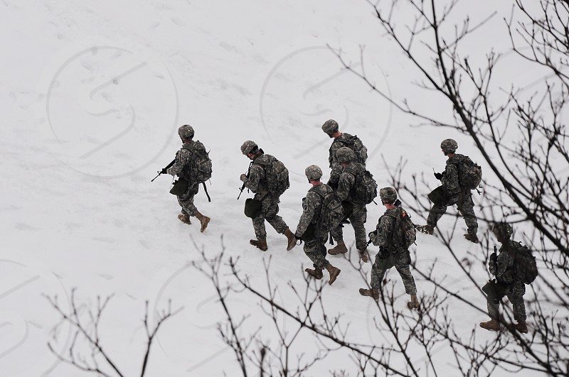 top view of 8 male military soldiers walking on snow during daytime photo