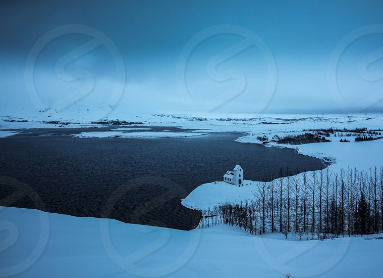 white building located by the lake under grey skies surrounded snow covered fields photo
