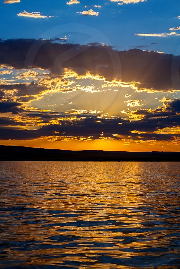 Sun streams as rays through an opening in clouds like a window to Heaven during sunset at Wahweap Bay of Lake Powell Arizona.  The sky goes from blue to gold and reflect in rippled water. photo