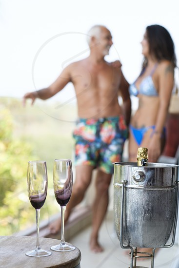 Man and woman in swimwear with champagne glasses and bottle in a cooler on a balcony photo